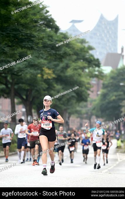 12 September 2021, Hamburg: Athletics: Marathon: Marathon runners in the Speicherstadt with the Elbphilharmonie in the background