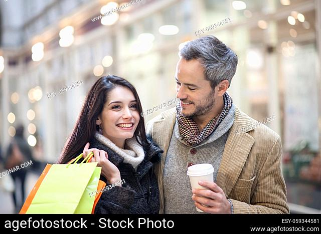 handsome couple doing shopping city lights in the background