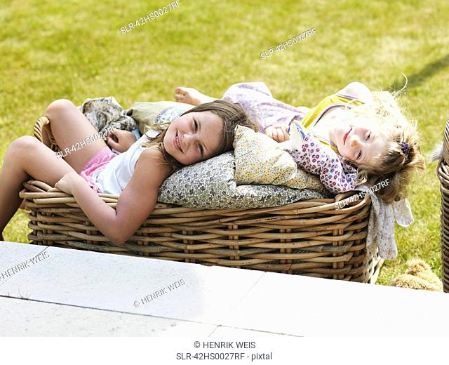 Girls relaxing in basket outdoors