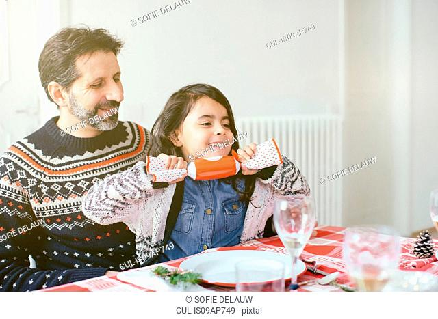 Girl with Christmas cracker at family Christmas party