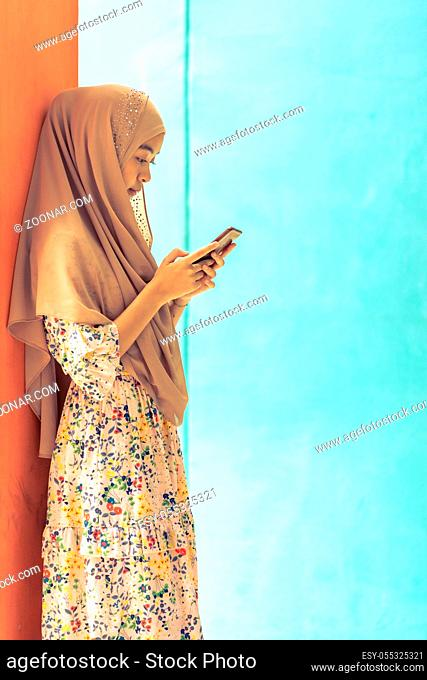 Young Adult Asian Thai Muslim university college student stand and using smart mobile phone. Unising for online education and technology concept