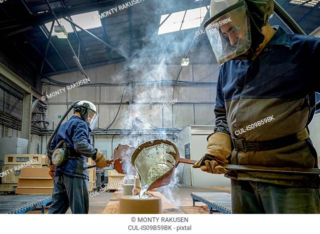 Workers pouring molten aluminium into moulds in precision casting factory