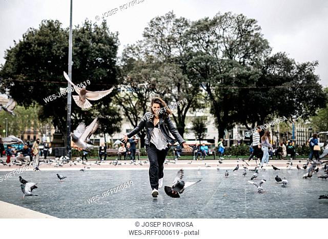 Spain, Barcelona, playful young woman with pigeons on a square