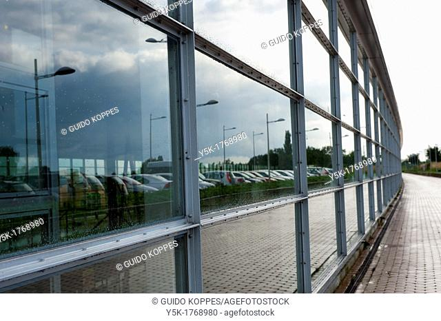 Barendrecht, Netherlands. Wall of glass, separating the train-station inside from the outside car-parking