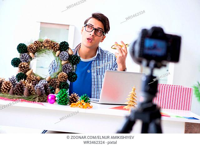 Young vlogger recording video doing christmas decoration
