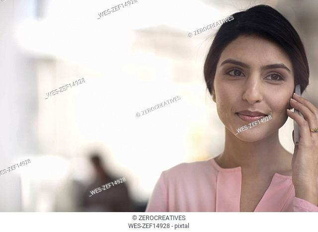 Portrait of smiling young woman on cell phone in the office