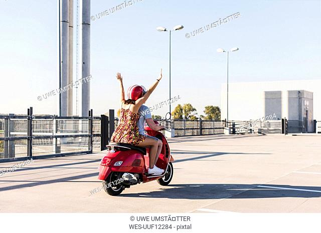 Carefree young couple riding motor scooter on parking level