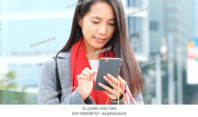 Young woman using mobile phone and holding shopping bag