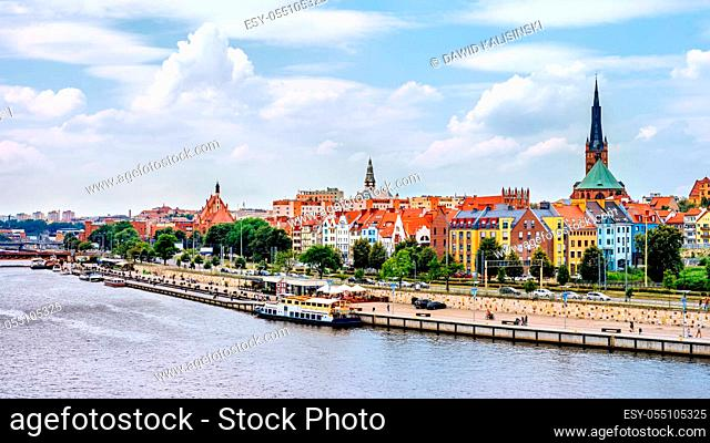 Ships anchored on Odra River pier. People relaxing on Piastowski Boulevard. Cathedral Basilica of St James the Apostle in background, Szczecin, Poland