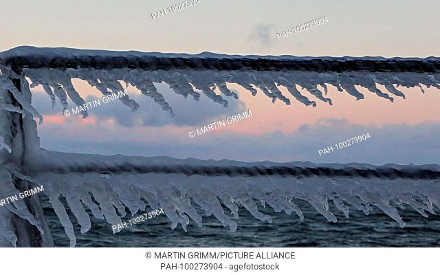 Huge icicles formed by waves hanging on frozen ship's rail, Baltic Sea, Mecklenburg-Western Pomerania, Germany | usage worldwide