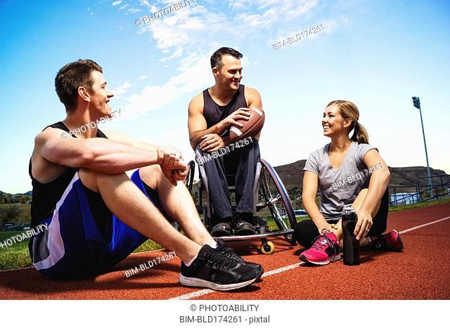 Paraplegic athlete in wheelchair and friends on track