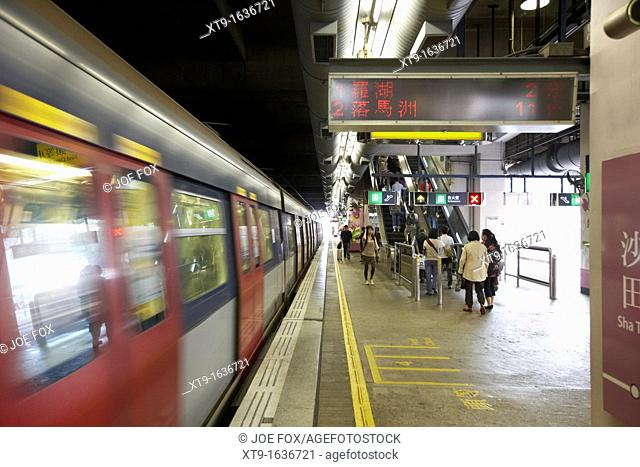 train leaving station at speed on mtr overground line former kcr kowloon canton railway hong kong hksar china asia