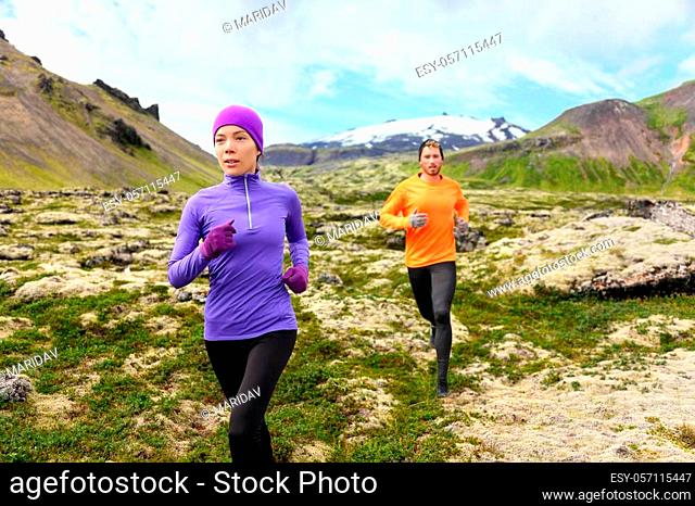 Running sport. Runners on cross country trail outdoors working out for marathon. Fit young fitness model man and asian woman training together outside in...