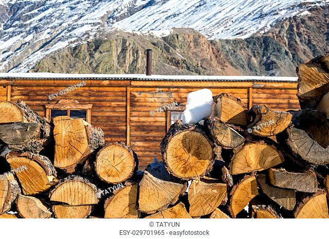 Stack of firewood at mountains background. Rural scene