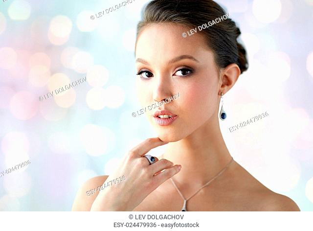 beauty, jewelry, people and luxury concept - beautiful asian woman or bride with earring, finger ring and pendant over blue holidays lights background