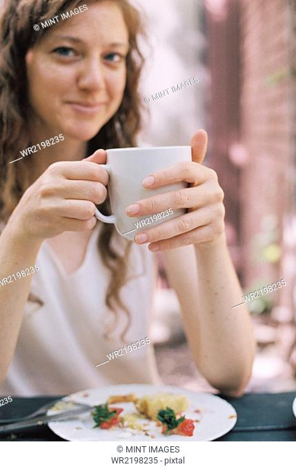 Smiling woman holding a white china teacup