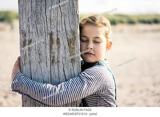 Little girl embracing wood pole with closed eyes