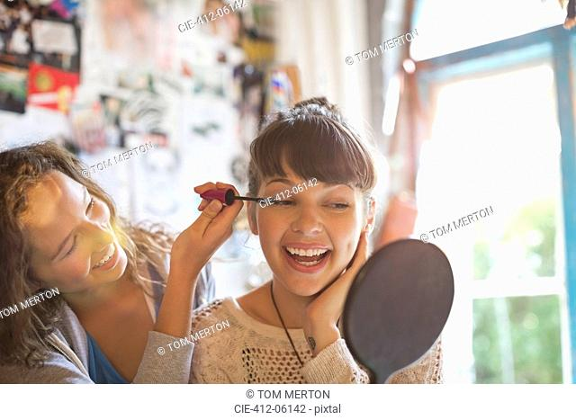 Woman applying makeup to friend's eyes in bedroom