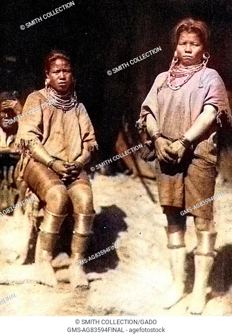 Two married women, with brass rings, cotton garters, and other valuable items provided by their husbands as a bride price, Myanmar (Burma), 1922