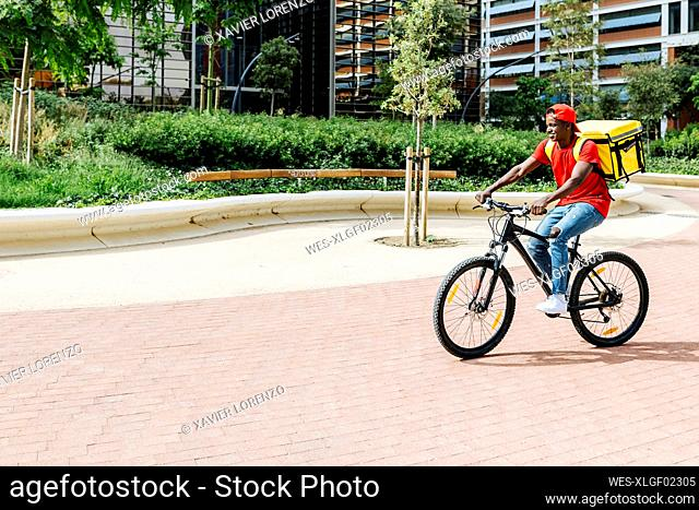 Delivery man wearing backpack cycling during sunny day