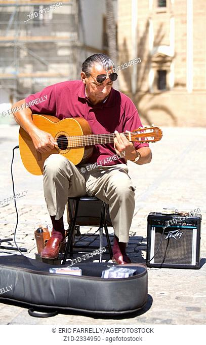 busker playing classical spanish guitar in the square in front of Cadiz Cathedral Spain