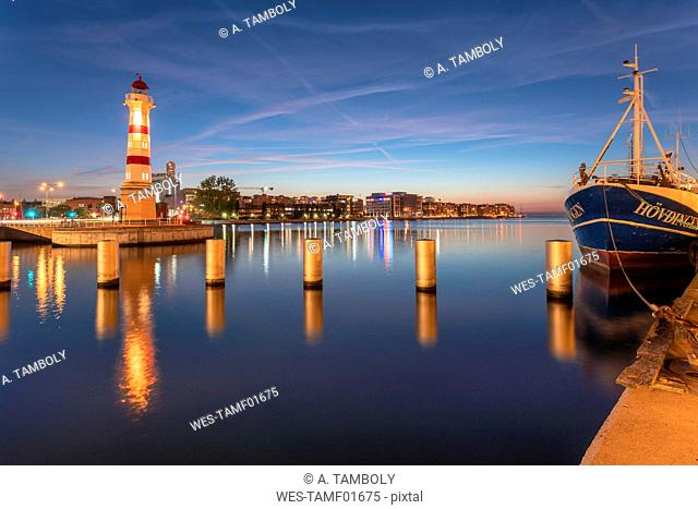 Illuminated lighthouse by river against sky at Malmo, Sweden
