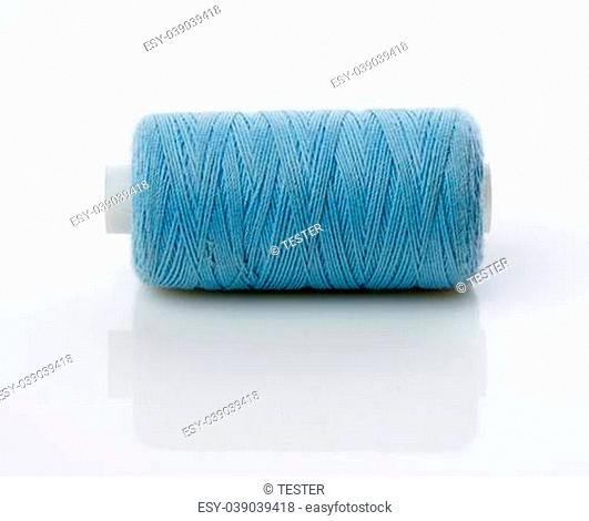 bobbin with blue thread on a white background