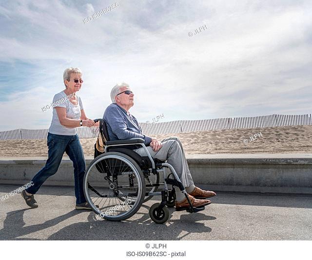 Senior woman pushing husband in wheelchair at beach, Santa Monica, California, USA
