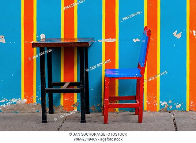 A wooden table with a cowhide chair are seen in front of the brightly paited facade of a colonial house in Jardín, a village in the coffee region (Zona...
