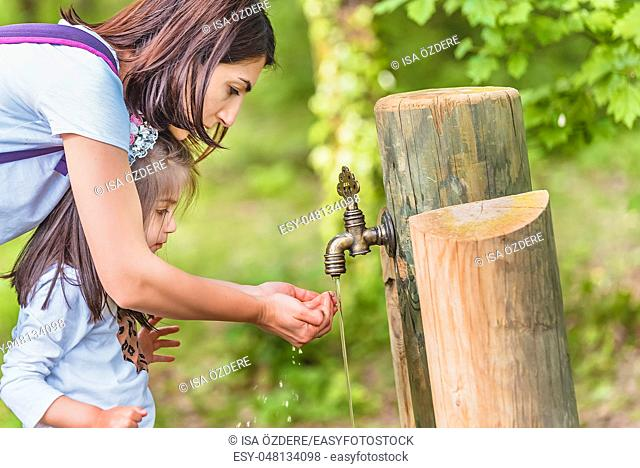 Young mom helps her little drinks water from a wooden tap in forest. Happy mother and daughter moments with love and natural emotion