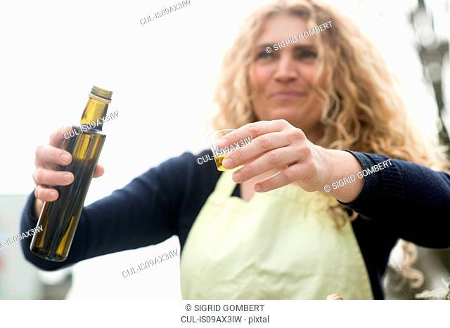 Market trader with bottle of olive oil