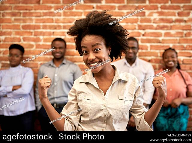 Smiling businesswoman flexing muscles with male and female coworkers in background at office