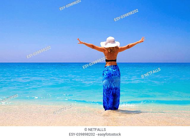 Woman on the beach wrapped in a sarong pareo and wearing a straw hat enjoying summer holidays