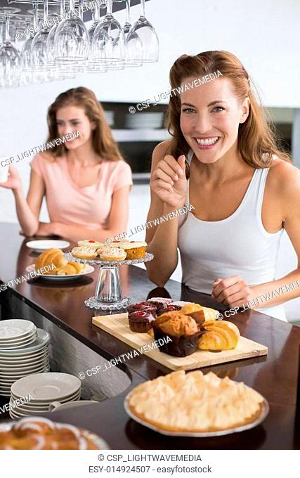 Smiling woman with sweet food at coffee shop
