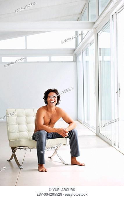 Handsome young man sitting on a chair laughing and smiling at you