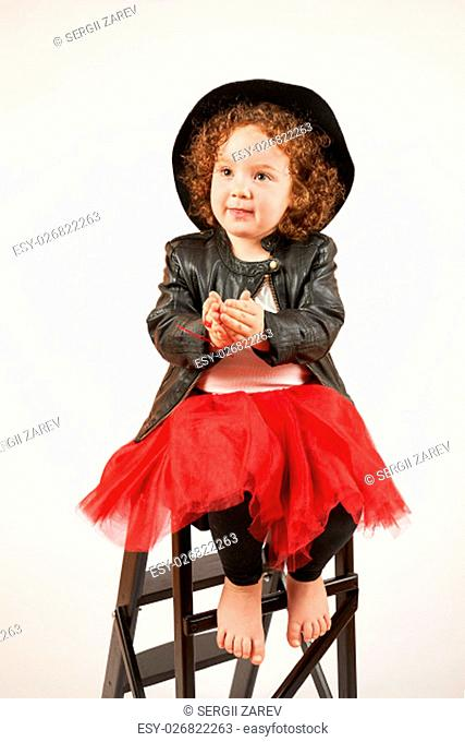 Little girl with black hat sitting and asks a toy