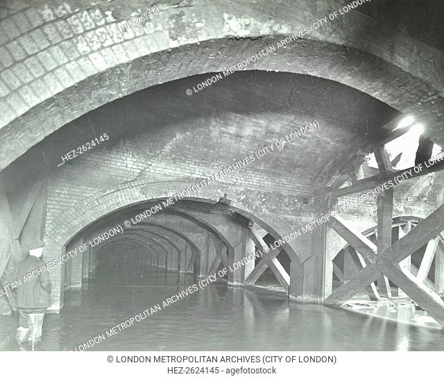Damaged interior of the underground reservoir, Beckton Sewage Works, London, 1938. Struts supporting a collapsing arch, with part of the roof missing