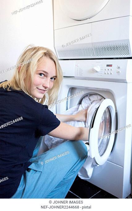 Smiling girl putting laundry in washing machine