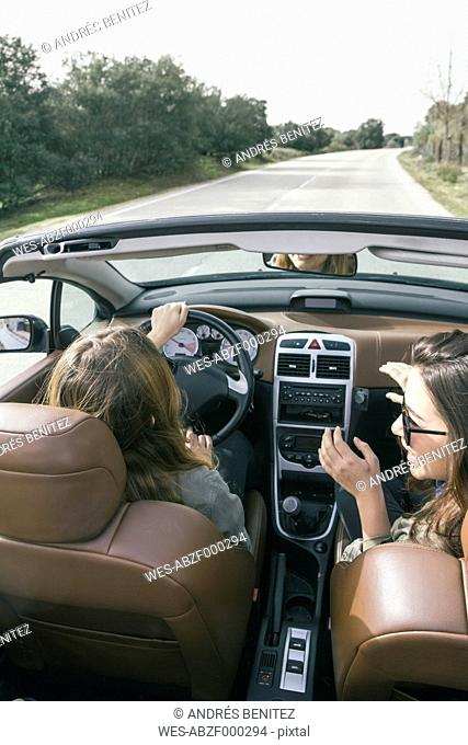 Woman driving a convertible car with her friend sitting on the passenger seat