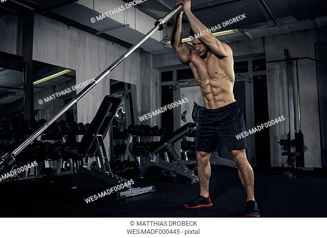 Physical athlete exercising with barbell