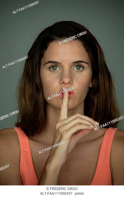Young woman holding finger against lips in silence, portrait