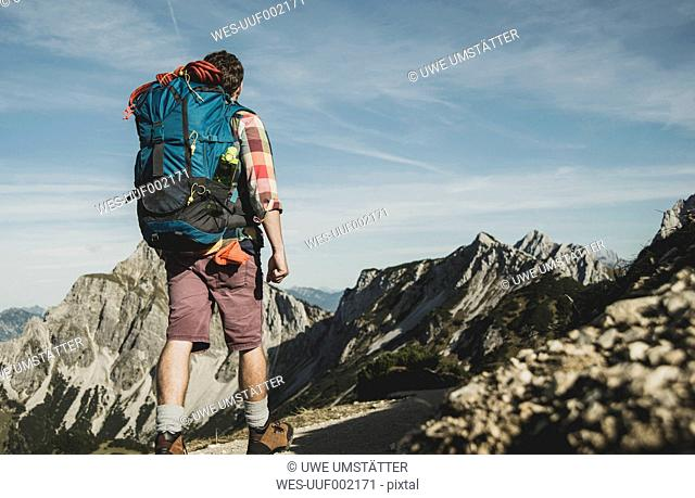 Austria, Tyrol, Tannheimer Tal, young man hiking on mountain trail