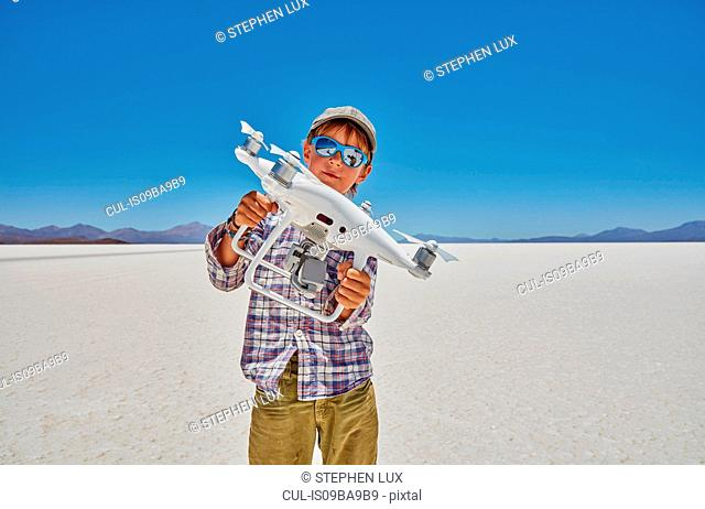 Portrait of boy on salt flats, holding drone, Salar de Uyuni, Uyuni, Oruro, Bolivia, South America
