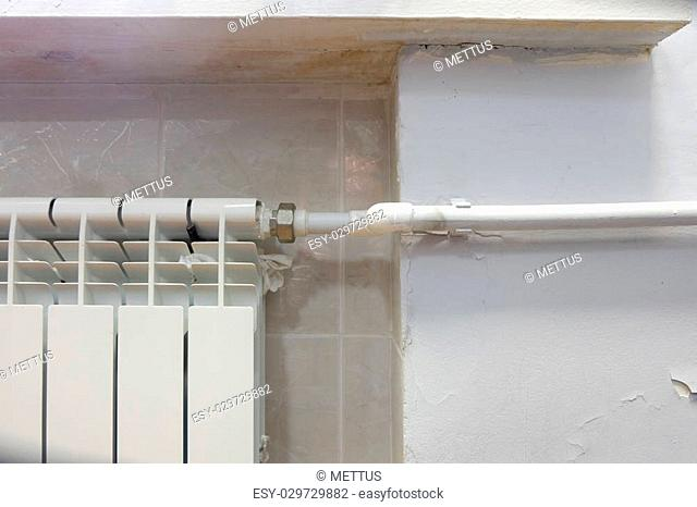 Part of the modern radiator and white plastic pipe, a lot of copyspace on wall