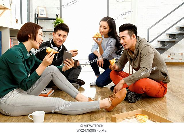 Business men and women eat pizza in the office