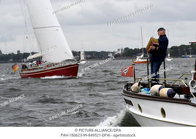 23 June 2018, Germany, Kiel: A man with a accordion accompanies the windjammer parade at the Kieler Woche (lit. Kiel Week) on the Fjord