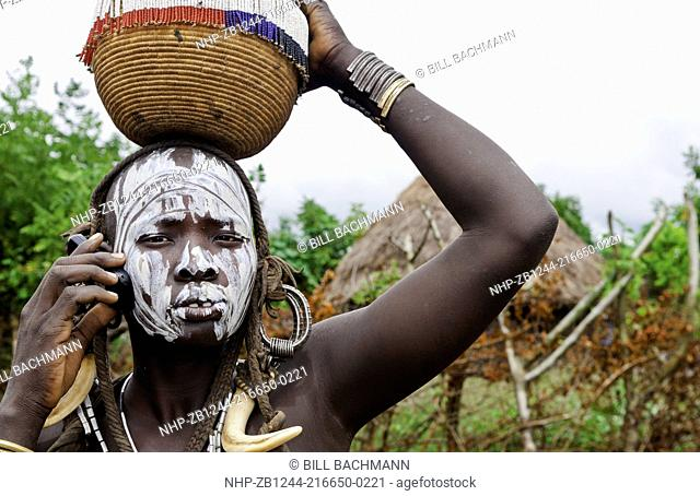 Jinka Ethiopia Africa village Lower Omo Valley Mago National Park wild tribe Mursi tribal woman with basket portrait on cell phone communicating with paint on...