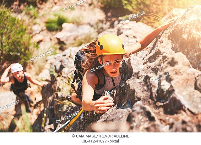 Focused, determined female rock climber hanging from rock