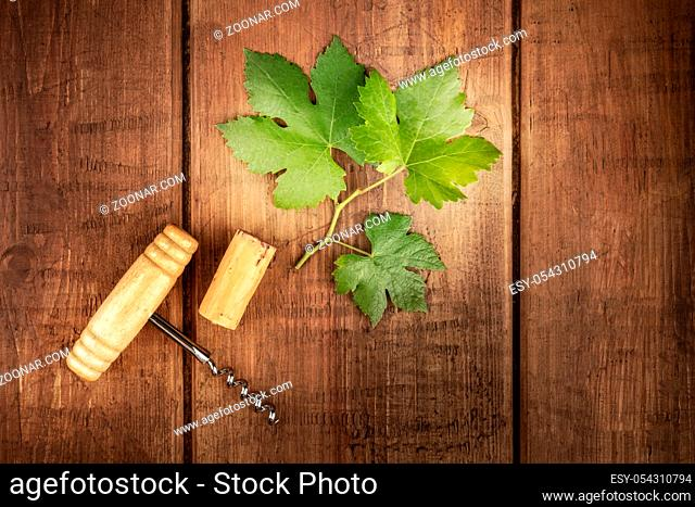 A vine leaf with a vintage corkscrew and a cork, shot from above on an oak barrel