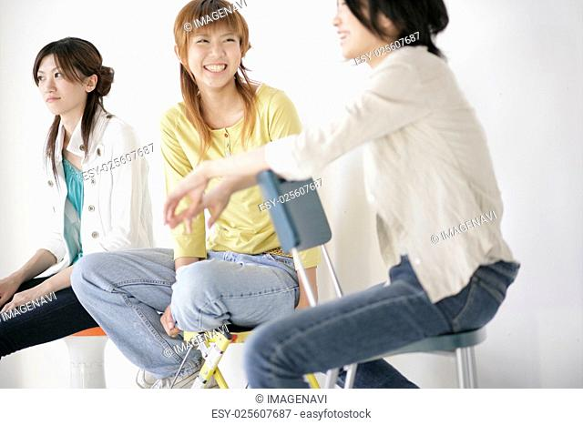 Young people sitting on chairs